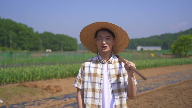 taking up farming - young man looking at camera and smiling while holding a agricultural equipment - 水田点の映像素材/bロール