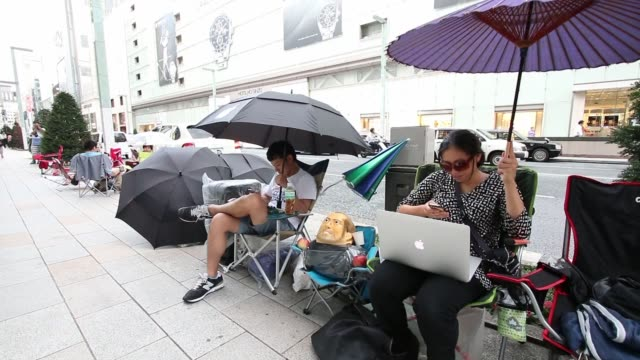 takuya kajigaya sits next to a mask resembling the late apple inc co founder steve jobs as he waits in line outside the apple store ginza ahead of... - apple computer stock-videos und b-roll-filmmaterial
