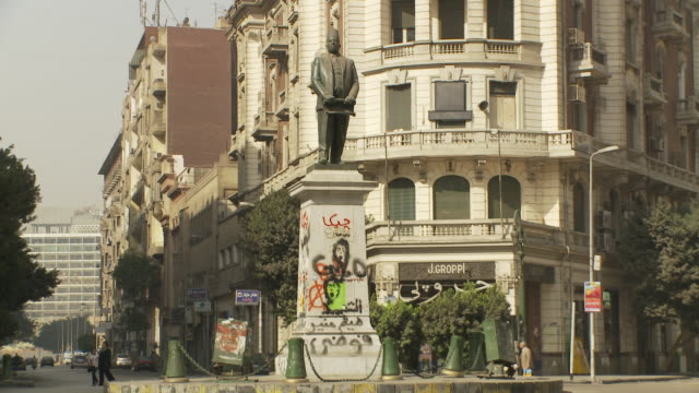 xws talaat harb statue standing on pedestal decorated w/ graffiti in midan w/ compact car passing right side up street few pedestrians apartment... - compact car stock videos and b-roll footage