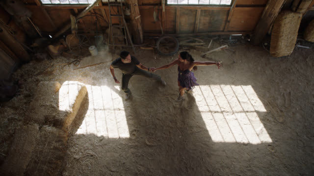 SLO MO. Talented ballroom dance partners approach each other and perform elegant routine in rustic barn setting.