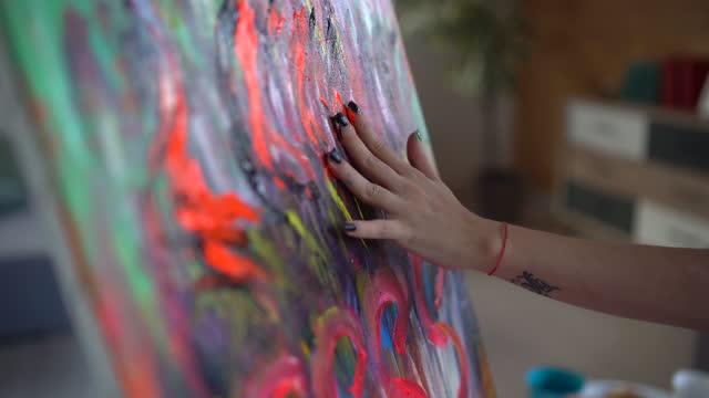 vídeos y material grabado en eventos de stock de artista femenina talentosa pintura con dedos sobre lienzo en estudio de arte - oficio creativo