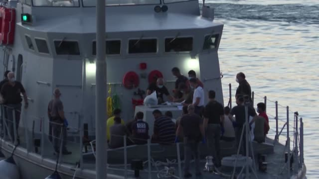 talian guardia di finanza police inspect migrants that arrived on the italian island of lampedusa on a fishing boat from tunisia - finanza stock videos & royalty-free footage