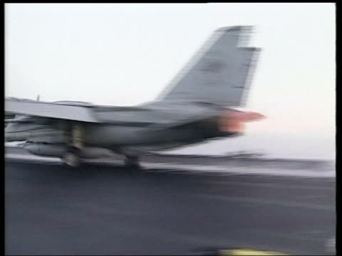 day 4 main events pool enterprise ext ms two flight deck crew crouching by wheels of fighter aircraft f14 takes off from deck of aircraft carrier pan... - grumman f 14 stock videos and b-roll footage