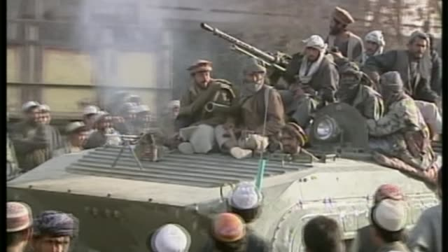 taliban gain control of kunduz lib ext gvs northern alliance troops atop tank as enter kunduz pan - 装甲車点の映像素材/bロール