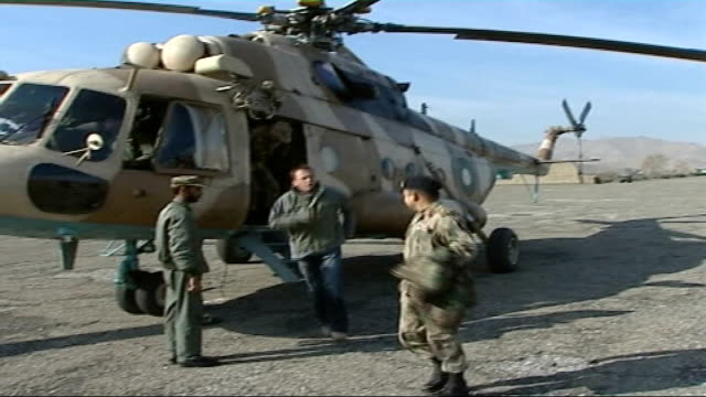 taliban supplying weapons across afghanistan border for attacks on uk and us soldiers; ext helicopters coming in to land reporter and sutan... - aussteigen stock-videos und b-roll-filmmaterial