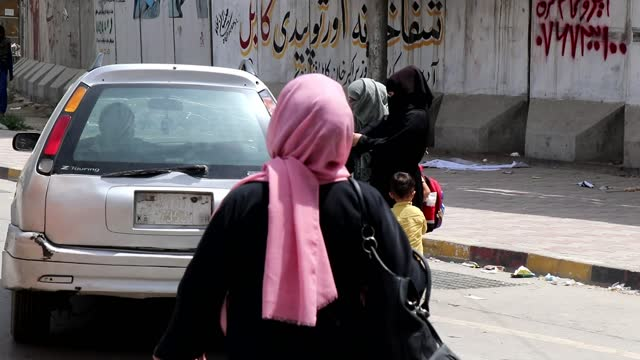 taliban takeover of afghanistan: fears over future of women's rights; afghanistan: kabul: ext gv woman in burkha along gv women in niqabs with child... - women stock videos & royalty-free footage