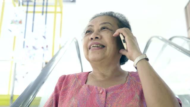 vídeos de stock e filmes b-roll de talking smartphone in shopping mall - 60 69 anos