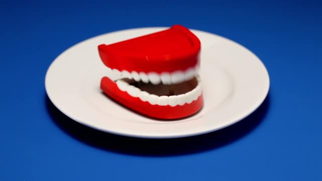 vidéos et rushes de parler dents sur une assiette - dents