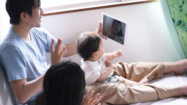 vídeos y material grabado en eventos de stock de talking to grandmother online, using tablet, on the bed - padres amos de casa