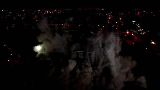 WS Tall apartment building is demolished in controlled implosion using explosives and dissappearing cloud of dust in  night / Sighthill, Scotland, UK