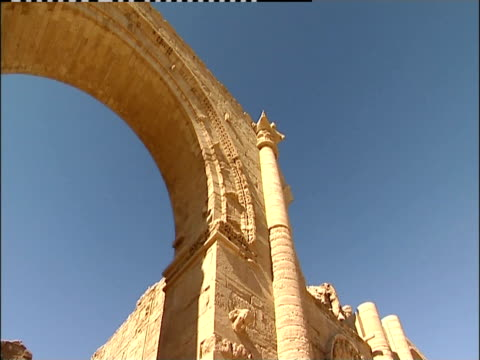 A tall arch towers over the facade of the Great Temple in Hatra, Iraq.