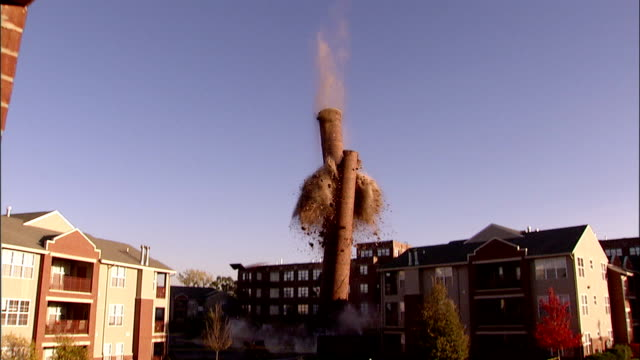 ws td  tall brick smokestack surrounded by houses is demolished using explosives and collapses / villa park, illinois, usa - demolished stock videos & royalty-free footage