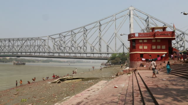 tall bridge over the holy river in kolkata (city of joy) - howrah bridge stock videos & royalty-free footage