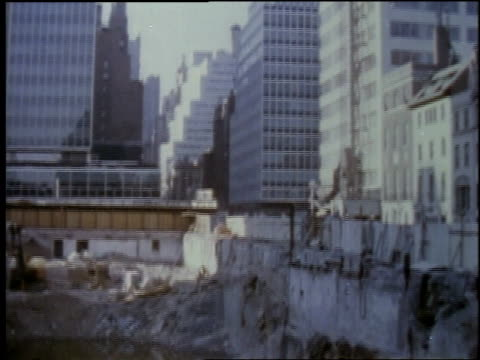 vidéos et rushes de 1957 ws tall building in a city, a puddle full of construction debris / united states - 1957