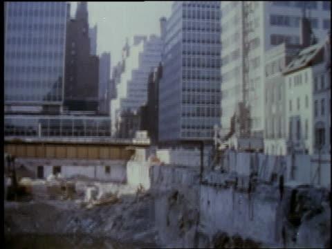 vídeos de stock e filmes b-roll de 1957 ws tall building in a city, a puddle full of construction debris / united states - 1957