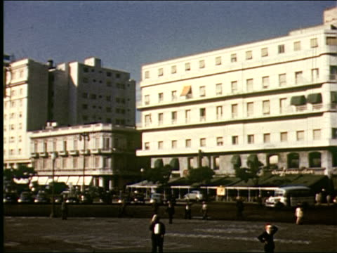 LS tall buildings across harbor / OS wide boulevard with cars buildings and park / Large open plaza / traffic and busy streets / Casa Rosada in Plaza...