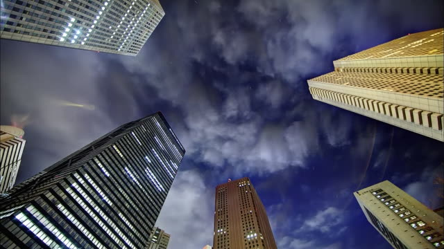 Tall buildings and the sky; Flowing clouds: SFX; Time Lapse.