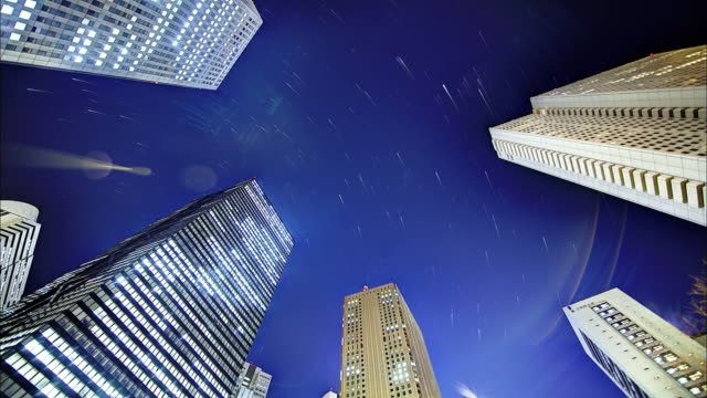 tall buildings and the star trajectory: sfx; time lapse. - sternenspur stock-videos und b-roll-filmmaterial