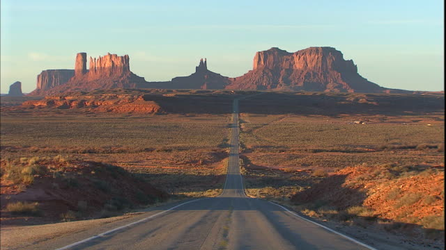 tall buttes tower beyond the highway in monument valley. - monument valley stock videos & royalty-free footage