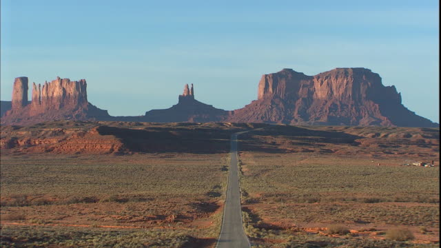 Tall buttes tower beyond the highway in Monument Valley.