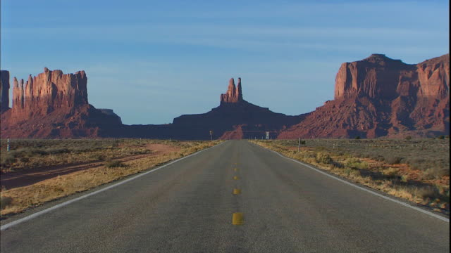 tall buttes tower beyond the highway in monument valley. - butte rocky outcrop stock videos and b-roll footage