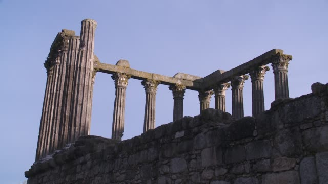 tall columns and stone walls comprise the ruins of a roman temple in evora. - évora district stock videos & royalty-free footage