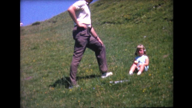 1964 tall dad and small child on hillside