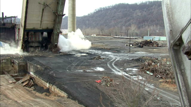 vidéos et rushes de ws tall factory building is demolished in controlled implosion using explosives / weirton, west virginia, usa - imploding