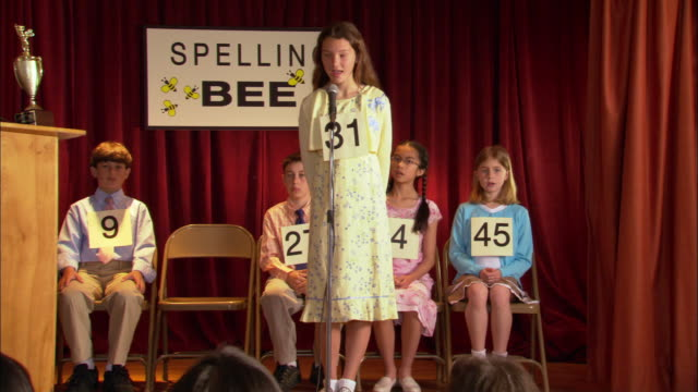 tall girl walking up to microphone and spelling word in spelling bee / girl with braids walking up to microphone and spelling word / los angeles, california - 背が高い点の映像素材/bロール