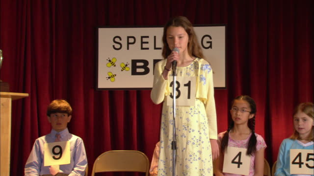 Tall girl walking up to microphone and spelling word in spelling bee / Los Angeles, California