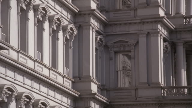 vídeos de stock e filmes b-roll de la a tall, gray office building with several windows lining each story embedded in intricate stone designs / washington, district of columbia, united states - frontão triangular