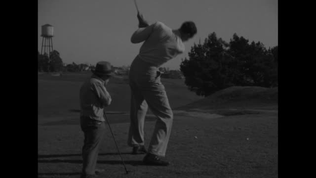tall man lock martin addresses golf ball at tee little person johnny puleo looks on martin swings and misses he then barely hits ball which just... - tall person stock videos and b-roll footage
