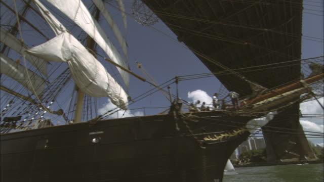 a tall ship sails beneath the sydney harbor bridge. - schiffsmast stock-videos und b-roll-filmmaterial