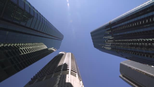 vidéos et rushes de les gratte-ciel de grande taille tournent rapidement à travers le cadre - avidité