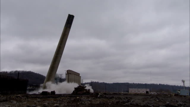 ws tall smokestack at an old power plant is demolished using explosives and falling / weirton, west virginia, usa - schornstein konstruktion stock-videos und b-roll-filmmaterial