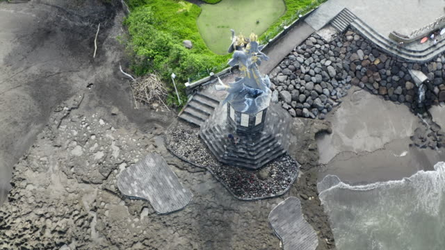 tall statue on rock formation at beach - canggu, bali - 突堤点の映像素材/bロール
