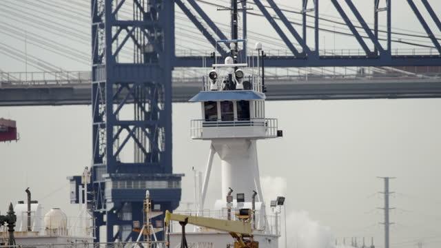 tall tugboat cruises past bridge in elizabeth nj - trade union stock videos & royalty-free footage
