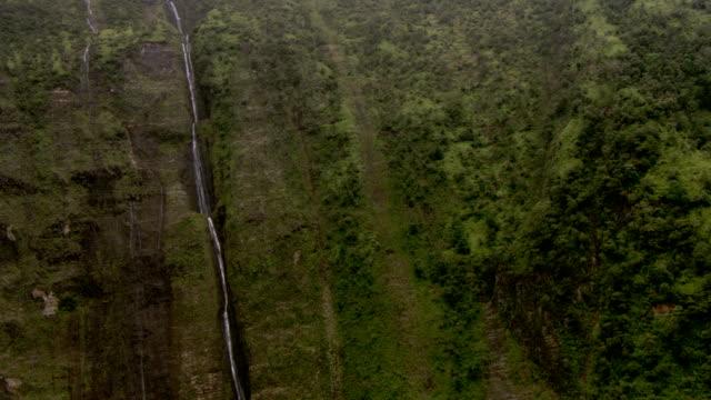 a tall waterfall pours into a deep valley. - vattenfall fallande vatten bildbanksvideor och videomaterial från bakom kulisserna