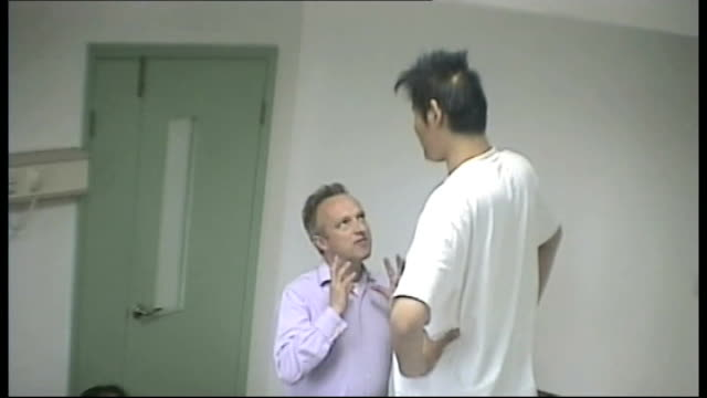 tallest man could enter record books; china: tianjin: int various shots of zhao liang standing beside reporter zhao liang interview sot - how can you... - traffic jam点の映像素材/bロール