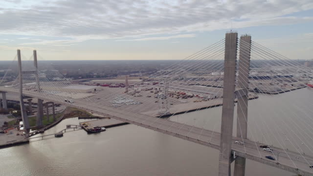talmadge memorial bridge over the savannah river, with a view of savannah in the backdrop, on the border between georgia and south carolina. cloudy fall early evening. aerial drone video with the panoramic wide-orbit camera motion. - georgia stati uniti meridionali video stock e b–roll