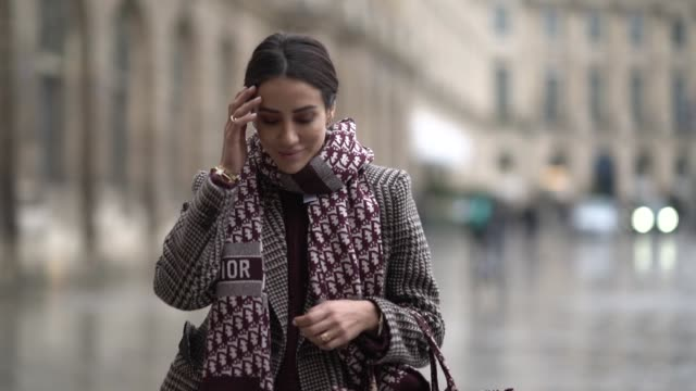 vídeos de stock e filmes b-roll de tamara kalinic wears a checked blazer jacket, a dior scarf, blue jeans, black leather high boots, holds a dior tote bag, outside alexis mabille,... - jaqueta jeans
