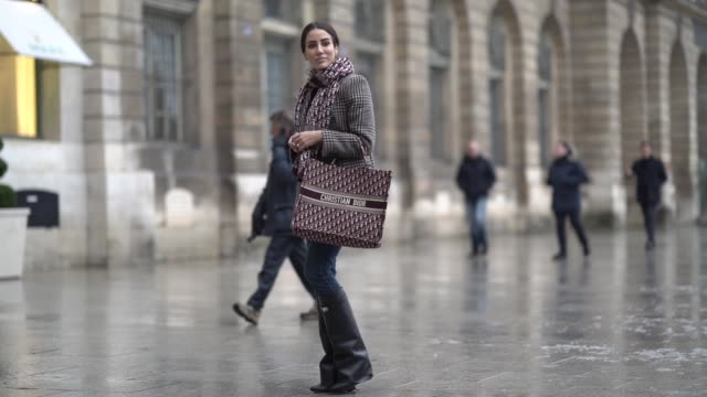 Tamara Kalinic wears a checked blazer jacket a Dior scarf blue jeans black leather high boots holds a Dior tote bag outside Alexis Mabille during...