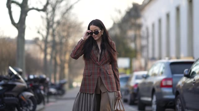stockvideo's en b-roll-footage met tamara kalinic wears a checked brown blazer jacket, sunglasses, a gray pleated skirt, a bag, during paris fashion week - haute couture spring/summer... - blazer