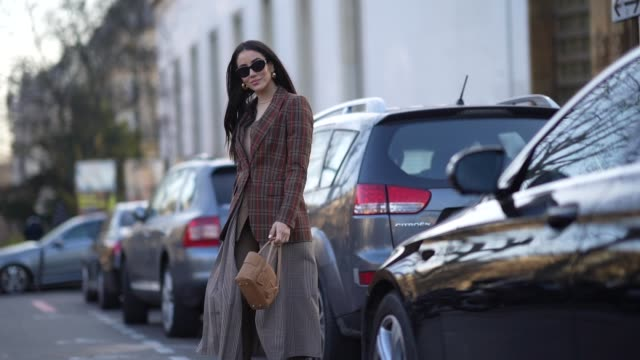 tamara kalinic wears a checked brown blazer jacket, sunglasses, a gray pleated skirt, a bag, during paris fashion week - haute couture spring/summer... - gray jacket stock videos & royalty-free footage
