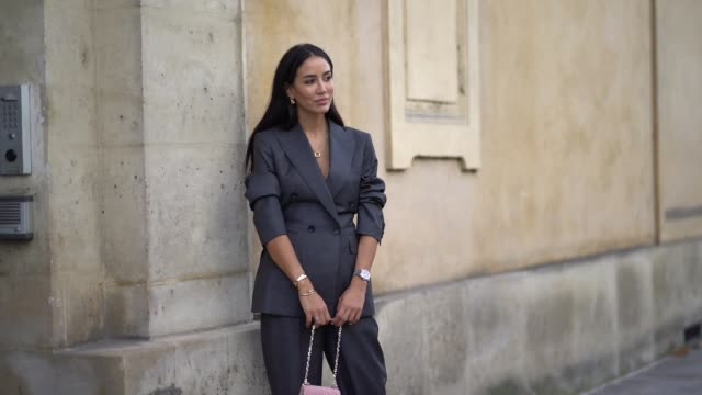 tamara kalinic wears a gray blazer jacket, a golden ring necklace, a pink bag, flare pants, earrings, outside beautiful people, during paris fashion... - gray jacket stock videos & royalty-free footage