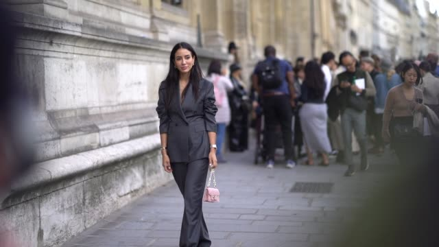stockvideo's en b-roll-footage met tamara kalinic wears a gray blazer jacket, a golden ring necklace, a pink bag, flare pants, earrings, outside beautiful people, during paris fashion... - blazer