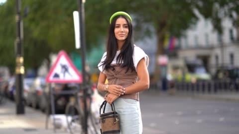 tamara kalinic wears a neon green headband, a white t-shirt, a brown fabric corset, a watch, golden bracelets, a vuitton brown monogram logo bag,... - t shirt stock videos & royalty-free footage