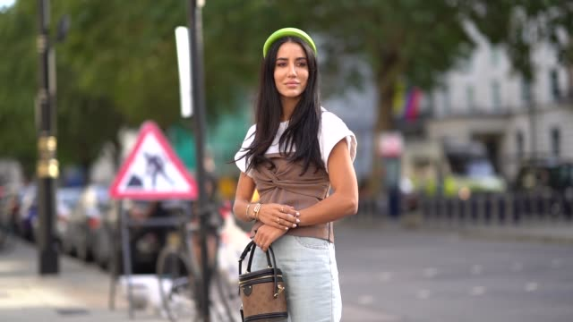 tamara kalinic wears a neon green headband, a white t-shirt, a brown fabric corset, a watch, golden bracelets, a vuitton brown monogram logo bag,... - maglietta video stock e b–roll