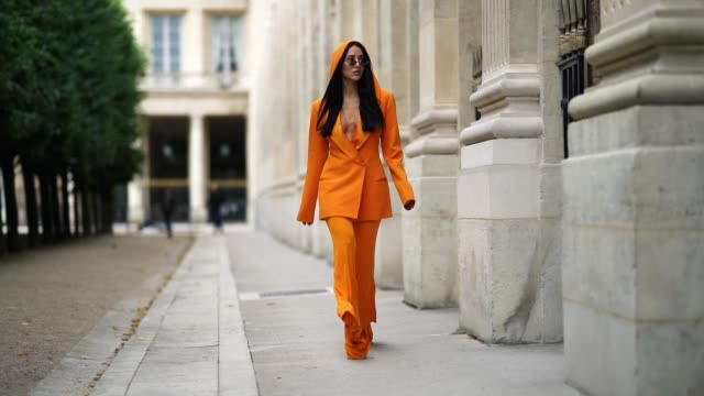 tamara kalinic wears an orange suit from balmain, featuring an oversized blazer jacket, flared flowing pants, a hood, ysl saint laurent shoes, linda... - street style点の映像素材/bロール