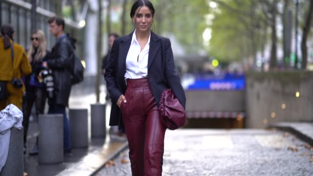 stockvideo's en b-roll-footage met tamara kalinic wears earrings, a white shirt, a navy blue pinstriped jacket, plum-color leather pants, a plum-color puff bag, black suede mules with... - modeweek